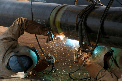 Natural gas pipeline being welded.